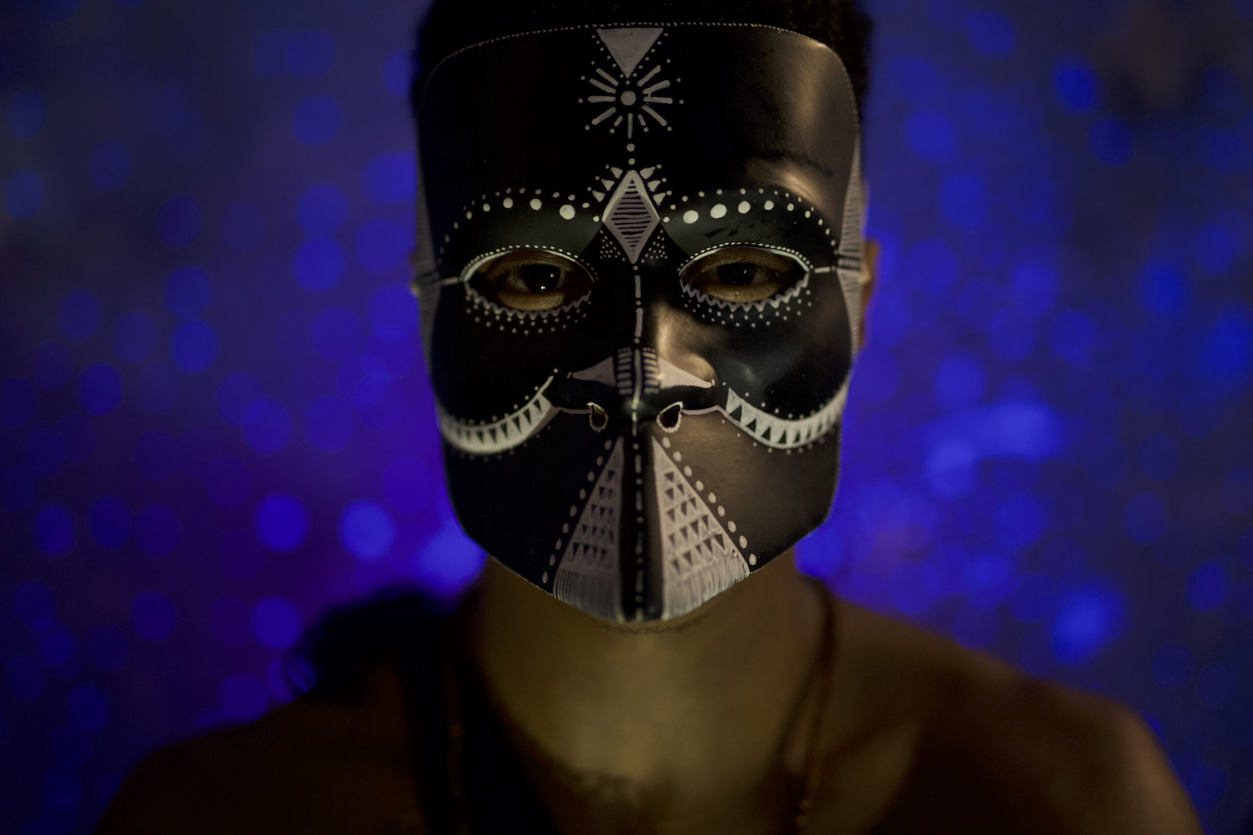 Homem sentado com máscara representando orixás em uma sala com fundo representando o universo